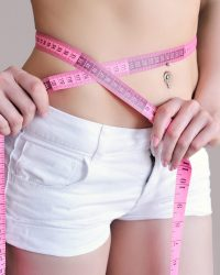 Close up of female hands measuring waist with measuring tape, dieting concept